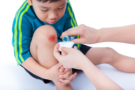 wound care: Little asian boy looking wound his leg, Nurse provides first aid,  on white background