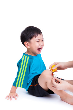 Portrait of a little asian boy (thai) crying, his mother provides first-aid at wound his leg, Isolated on white background Stock Photo