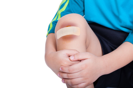 contusion: Child knee with a plaster (for wounds) and bruise, Isolated on white background
