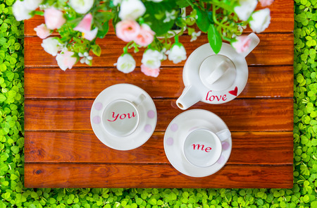 drink me: Top view of the teapot, empty teacup or coffee cup and artificial flowers on a wooden and green clover, Love of you and me concept