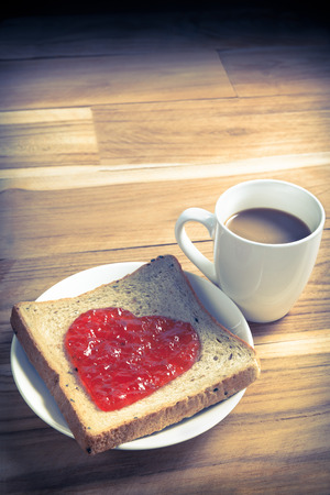 Delicious slice of bread with strawberry jam heart shape and cup of coffee on wooden background  for a Valentines day, love concept, colorized vintage picture style photo