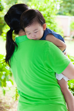 Mother carrying her daughter in backyard over blur green nature background, little asian girl (thai) sleeping on her mother shoulder