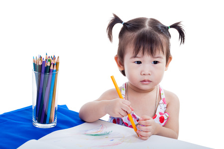 Little asian (thai) girl imagine to draw picture at the table with images paper and colour pencils, isolated on white background photo