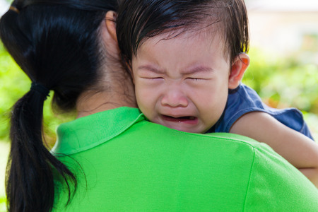 30 35 years: Mother carrying and comfort her daughter in backyard over blur green nature background, little asian girl (thai) crying on her mother shoulder Stock Photo