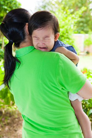 Mother carrying and comfort her daughter in backyard over blur green nature background, little asian girl (thai) crying on her mother shoulder Stock fotó
