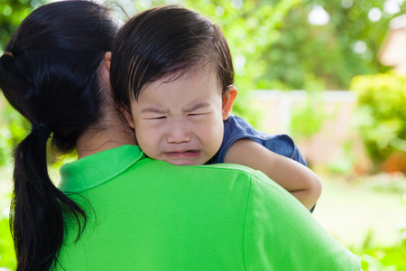 Mother carrying and comfort her daughter in backyard over blur green nature background, little asian girl (thai) crying on her mother shoulder Stock Photo