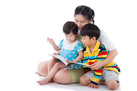 Image of cute young female with two little asian children reading a book together, daughter sitting on the lap, son sitting on the floor, happy family concept, isolated on white background Stock Photo