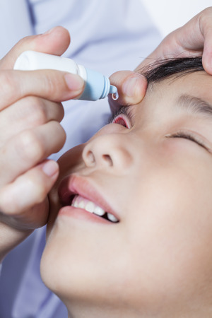 Closeup of doctor pouring eye drops in sick children conjunctivitis eyes