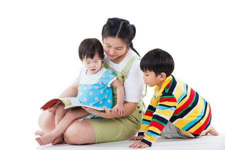 Image of cute young female with two little asian children reading a book together, daughter sitting on the lap, son sitting on the floor, happy family concept, isolated on white background Banque d'images