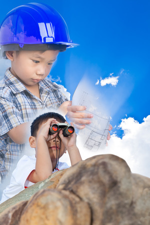 thai boy: Future engineer, little asian (thai) boy lying prone on a boulder and using binoculars to view on blue sky background, conceptual image about education, imagine and occupation in the future Stock Photo