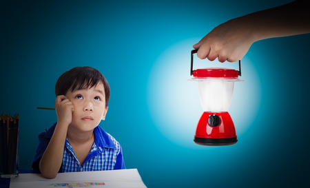 Asian (thai) boy thinking and looking up emotion at the table with images paper and colour pencils. Hand woman holding plastic electric lantern with lit flame on blue background, concepts of searching and direction photo