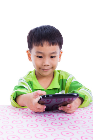 thai boy: Little asian (thai) boy smiling and using digital tablet pc at desk