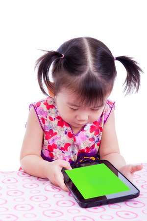 Adorable little asian (thai) girl using digital tablet at desk photo