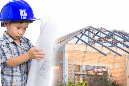 Dream of the child's future career (engineer). Little asian (thai) boy with blue helmet and blueprint, house of brick still under construction background, conceptual image about education