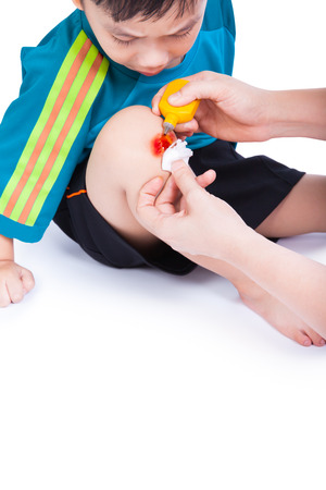 Little asian (thai) boy looking wound his leg, Nurse provides first aid, shoot in studio, Isolated on white background