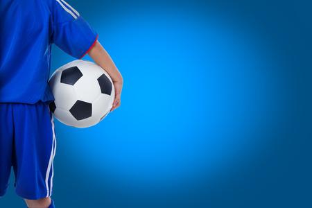 football players: Volver la vista de jugador de f�tbol juvenil en el uniforme azul y peque�o ni�o sosteniendo una pelota. Algunos espacio para el mensaje de texto de entrada en el fondo azul Foto de archivo