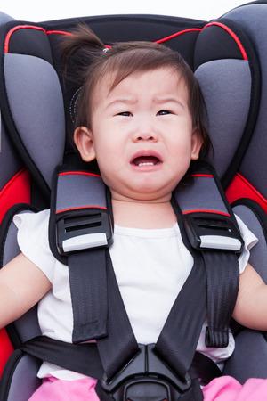 ni�o llorando: Imagen de la ni�a asi�tica (thai) llorando y se sujeta con el cintur�n de seguridad en la seguridad del coche-asiento. Concepto sobre la seguridad de los que viajan en coche, ni�os y beb� Foto de archivo