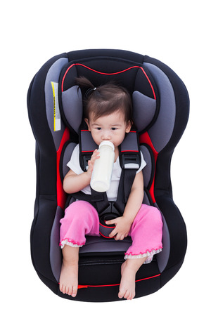 Image of little asian (thai) girl suck up milk and fastened with security belt in safety car-seat, Isolated on white background. Concept about the safety of traveling by car, children and baby 版權商用圖片