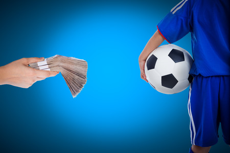 Back view of youth soccer player in blue uniform and little kid holding a ball and hand holding stacks of banknotes on blue background, concept about corruption or bribery of match of soccer photo