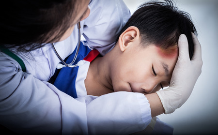 contusion: Youth asian (thai) soccer player in blue uniform. Child temple with a bruise, doctor perform first aid by checking. Shoot in studio. Low key lighting picture style
