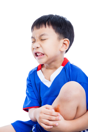 painfully: Youth asian (thai) soccer player in blue uniform sitting. Expression of painfully. Child shin with a bruise, isolated on white background. Studio shot Stock Photo