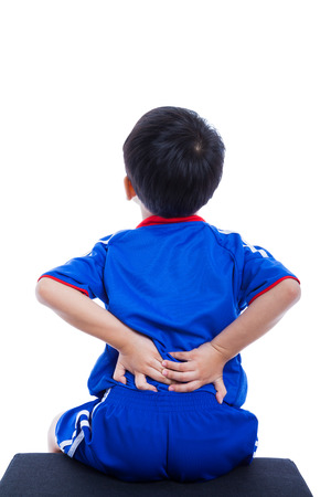 low back: Back pain. Athlete little asian (thai) boy in blue sportswear rubbing the muscles of his lower back, cropped torso portrait, isolated on white background. Studio shot
