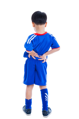 low back: Back pain. Athlete little asian (thai) boy in blue sportswear standing and rubbing the muscles of his lower back, isolated on white background. Studio shot