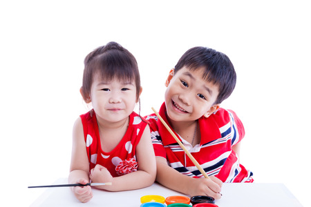 Little asian (thai) children happily, brother and sister looking at the camera and smiling, holding a paintbrush, Concepts of creativity and education. Isolated on white background. Studio shot photo