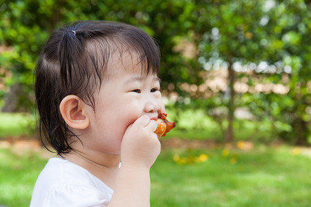 Closeup adorable little asian (thai) girl enjoy eating her lunch in the park, child eating fried chicken over blur green nature background photo