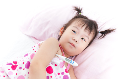 Little asian (thai) girl lying on sickbed with digital thermometer in her armpit, child with fever digital meter show 38.2 celsius is high temperature for human. Studio shot