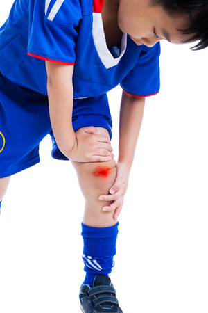 Youth asian (thai) soccer player in blue uniform painful. Child knee with a bruise, isolated on white background. Studio shot