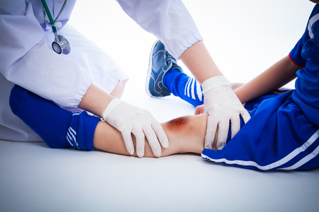 injurious: Youth soccer players knee with a bruise, left knee bruise. Doctor perform checking and first aid at knee trauma. Studio shot Stock Photo