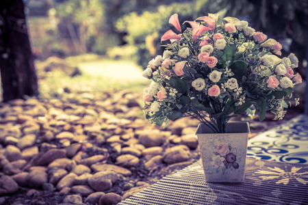 Beautiful bouquet of artificial flowers in a ceramic vase in park background, colorized vintage picture style photo