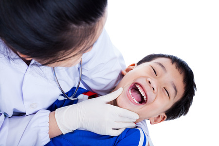 Young dentist checking oral health of child. Cute sport boy opening his mouth wide during inspection of oral cavity and smiley face, isolated on white background photo