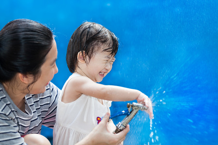 affectionate action: Funny laughing little asian (thai) girl and her mother playing with water hose at the day time, on blue background, loving and happy family