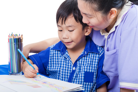 Little asian boy sitting at the table and drawing picture by colour pencil, mother teach her son. Learning, education of art and creativity concept, studio shot Stock Photo
