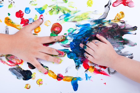 Closeup of little children hands doing finger painting with various colors on white background, art education and creativity concept, top view