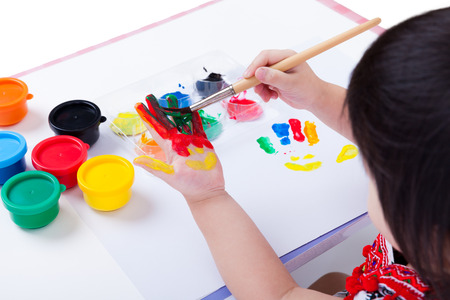 Little asian (thai) girl painting her palm using multicolored drawing tools (watercolor paints, paintbrush), learning, education of art and creativity concept, studio shot