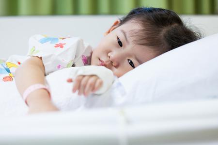 Illness little asian (thai) girl lying on a sickbed in hospital, saline intravenous (IV) on hand