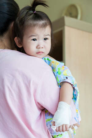 Mother carrying her daughter,  illness child in hospital, saline intravenous (IV) on hand asian girl photo