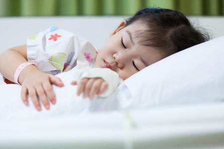 bebe enfermo: Niña asiática (thai) dormido en un lecho de enfermo en el hospital Enfermedad, intravenosa de solución salina (IV) en la mano