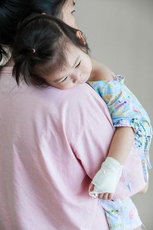 Madre que lleva a su hija, la enfermedad del niño en el hospital, intravenosa de solución salina (IV) en la mano chica asiática