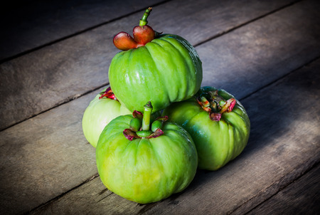 Still life with fresh garcinia cambogia on wooden background. Garcinia is thai herb (south of Thailand) and sour flavor lots of vitamin C. Low key picture style Banque d'images
