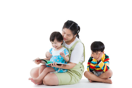 Image of cute young mother with two little asian children (full body), daughter smiling and reading book, son feel bad and sitting on the floor(different gesture), some space for input text message. Isolated on white background photo