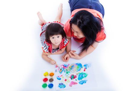 spielen: Portrait der kleine asiatische (Thai) Mädchen mit Malerei und Malwerkzeuge (Aquarellfarben, Pinsel) mit ihrer Mutter in der Nähe, auf weißem Hintergrund. Kreativität Konzept. Studio shot. Aufsicht