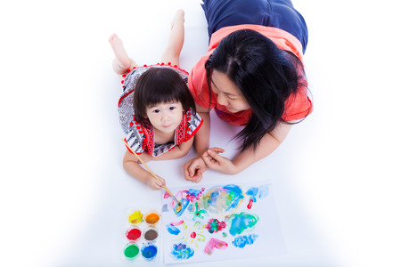 Portrait of little asian (thai) girl painting and using painting tools (watercolor paints, paintbrush) with her mother near by, on white background. Creativity concept. Studio shot. Top view Stock Photo
