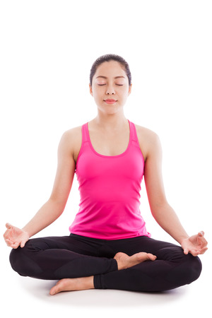 Portrait of a beautiful young asian (thai) woman practicing yoga, sitting in a lotus position isolate on white background