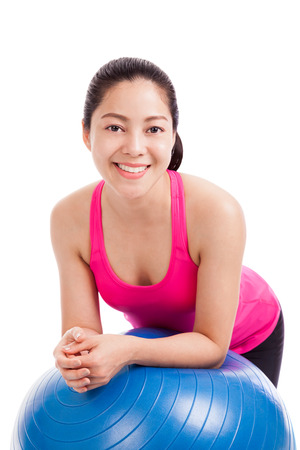 Healthy woman  beautiful girl smiling and leaning on a fitness ball in a fitness studio isolated on white background model is asian girl photo
