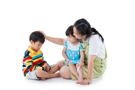 Image of mother with two little asian thai children full body daughter sitting on lap son feel bad mom comforting. Great parenting image. Problems in the family. Isolated on white background