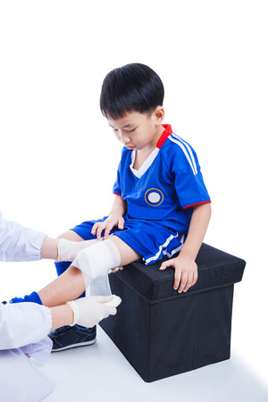 injurious: Youth asian (thai) soccer player in blue uniform. Doctor perform first aid knee injure by bandage, knee have bruise. Studio shot. Isolated on white background Stock Photo